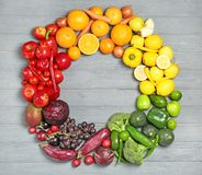 Rainbow frame made of fresh fruits and vegetables. On wooden background Royalty Free Stock Photo
