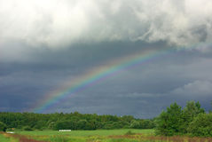 Rainbow in front of a dark Rain Clouds Stock Image