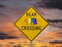 Rainbow Gay Pride Flag Bear Crossing Sign with Sunset Sky. Rainbow gay pride flag bear crossing highway sign with sunset sky stock photo