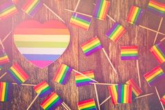 Gay pride. Rainbow Gay Pride small flags on wood background stock photo