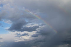 Rainbow in the gray white clouds against the blue sky, close-up Stock Image