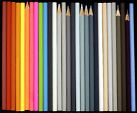 Rainbow and grey colored pencils. A diverse assortment of new and used colored pencils on black Stock Image