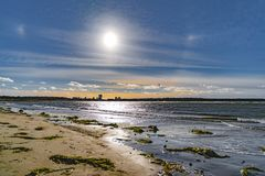 A Rainbow halo around the sun in blue evening sky. Rainbow halo around the sun in blue evening sky above baltic sea beach stock image