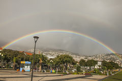 A rainbow with a halo over the hills of Funchal, Madeira. Royalty Free Stock Image