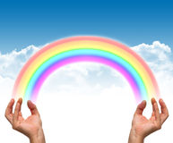 Rainbow and hands. Among clouds stock photos