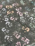 Rainbow hands on pavement Royalty Free Stock Images