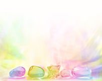 Rainbow Healing Crystals. Row of Rainbow Healing Crystals on a pastel gradient rainbow colored background Stock Photos