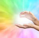Rainbow healing energy field. Female outstretched healing hands on soft radiating rainbow energy formation background Stock Image
