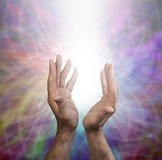 Rainbow Healing Energy. Male Healer's hands with outstretched hands and shaft of light on a muted rainbow web background Royalty Free Stock Photo