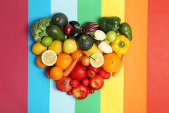 Rainbow heart made of fruits and vegetables. On color background Royalty Free Stock Image