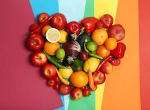 Rainbow heart made of fruits and vegetables. On color background Stock Image