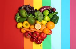 Rainbow heart made of fruits and vegetables. On color background Royalty Free Stock Images