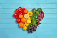 Rainbow heart made of fruits and vegetables. On wooden background royalty free stock images