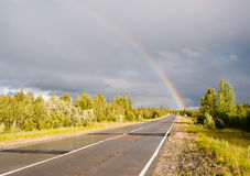Rainbow  on highway. Cloudy sky and rainbow on highway Royalty Free Stock Photo