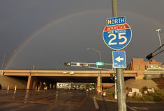 Rainbow with Highway and Interstate Sign in America. A large rainbow spans the highway of a southwestern American city after a rainstorm, while a sign points the Royalty Free Stock Images