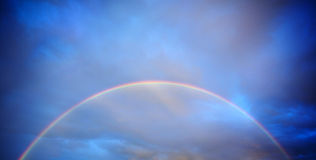 Rainbow infront of sunset sky Royalty Free Stock Image