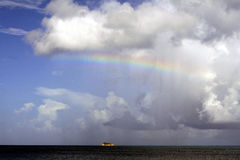 Rainbow Island. A rainbow hovers over a tiny island near Antigua Stock Photo