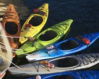 Rainbow of Kayaks. Brighly colored Kyayks waiting for use stock photos