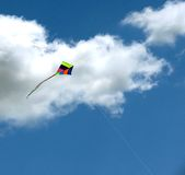 Rainbow Kite. A kite with the colours of a rainbow soars up to the clouds on a summer's day stock photo
