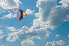 Rainbow kite flies in the blue sky Royalty Free Stock Images