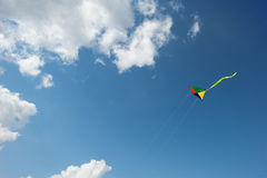 Rainbow kite flies in the sky among the clouds Royalty Free Stock Photo