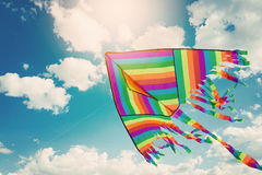 Rainbow kite flying in blue sky with clouds. Freedom and summer holiday stock image