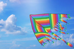Rainbow kite flying in blue sky with clouds. Freedom and summer holiday. Concept royalty free stock photo