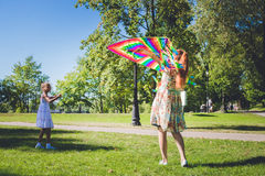 Rainbow kite in the sky. Two girls playing with kite. Mother and her dother Stock Photos