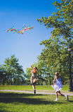 Rainbow kite in the sky.  Two girls playing and running with kite. Stock Photos