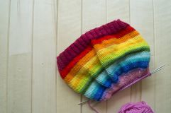 Rainbow knitted hat, handmade. Favorite domestic hobby. Wooden background. The comfort in the house. Basket with balls of threads Royalty Free Stock Image