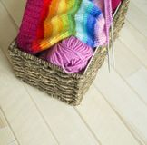 Rainbow knitted hat, handmade. Favorite domestic hobby. Wooden background. The comfort in the house. Basket with balls of threads Stock Images