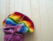 Rainbow knitted hat, handmade. Favorite domestic hobby. Wooden background. The comfort in the house. Basket with balls of threads Stock Photography