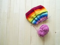 Rainbow knitted hat, handmade. Favorite domestic hobby. Wooden background. The comfort in the house. Basket with balls of threads Stock Photo