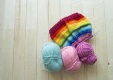 Rainbow knitted hat, handmade. Favorite domestic hobby. Wooden background. The comfort in the house. Basket with balls of threads Royalty Free Stock Photo
