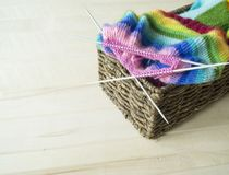 Rainbow knitted hat, handmade. Favorite domestic hobby. Wooden background. The comfort in the house. Basket with balls of threads Stock Photos