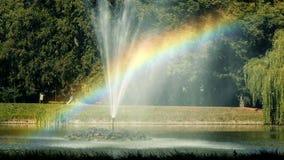 Rainbow Lake. Fountain in a lake creates a rainbow stock footage
