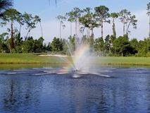 Rainbow in lake fountain on a golf course stock images