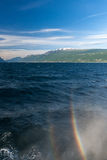 Rainbow on a lake Garda with mountains as Royalty Free Stock Images