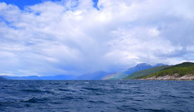 Rainbow on land. Image of a rainbow on land, with storm clouds and fussy sea royalty free stock images