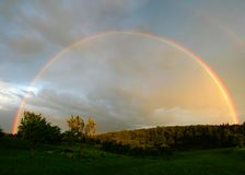Rainbow landscape. Rainbow in the cloudy sky Stock Photo