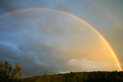 Rainbow landscape. Rainbow in the cloudy sky Stock Photos
