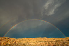 Rainbow landscape. Landscape with a colorful rainbow in stormy sky, Kalahari desert, South Africa stock photography