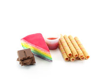 Rainbow layer cake and strawberry roll with chocolate dessert. On white background Royalty Free Stock Images
