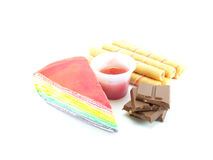 Rainbow layer cake and strawberry roll with chocolate dessert on white background Royalty Free Stock Photography