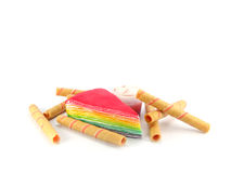 Rainbow layer cake. And strawberry roll on white background Stock Photos