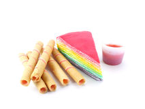 Rainbow layer cake and strawberry roll on white background Royalty Free Stock Photos
