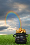 Rainbow leading to pot of gold. In the grass Stock Images