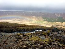 Rainbow leading into village below mossy cliffs in Iceland. On a drizzly day in the west Icelandic countryside, a rainbow is visible in the valley from the mossy Royalty Free Stock Images