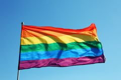 Rainbow LGBT flag fluttering. On blue sky background. Gay rights movement stock photos
