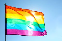 Rainbow LGBT flag fluttering. On blue sky background. Gay rights movement royalty free stock photos